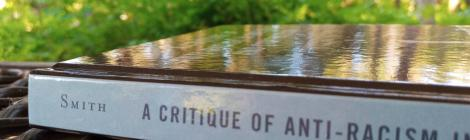 A photo of Erec Smith's book A Critique of Anti-Racism in Rhetoric and Composition, sitting on a picnic table, with green leaves in the background